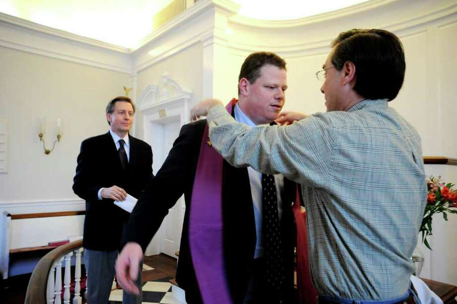 Sean Witty, new associate pastor, center, receives a stole from Chis Cole, while Steve Pisarkiewicz, lay leader, left, watches, at the installation at the First Church of Round Hill, on Sunday, Feb. 27, 2011. Photo: Helen Neafsey / Greenwich Time