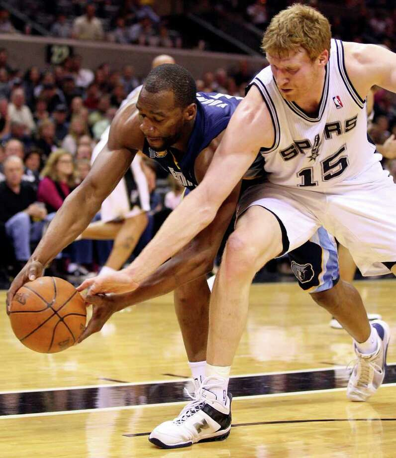 FOR SPORTS - Spurs' Matt Bonner and Grizzlies' Sam Young grab for a loose ball  during first half action Sunday Feb 27, 2011 at the AT&T Center.  (PHOTO BY EDWARD A. ORNELAS/eaornelas@express-news.net) Photo: EDWARD A. ORNELAS, SAN ANTONIO EXPRESS-NEWS / eaornelas@express-news.net