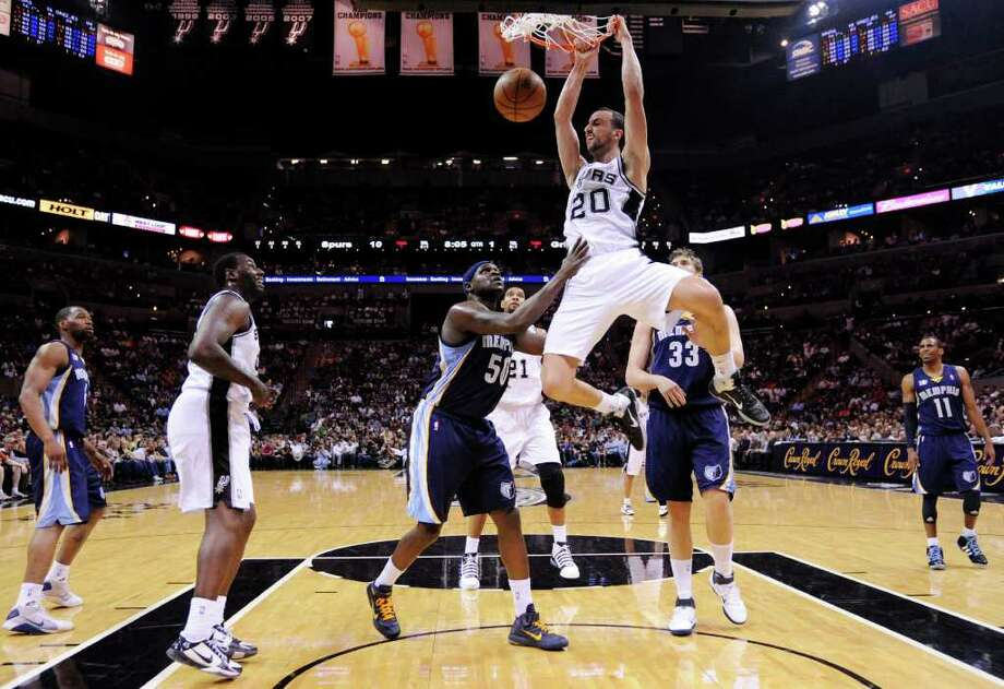 FOR SPORTS - Spurs' Manu Ginobili hangs on the rim after a dunk over the Grizzlies' Zach Randolph during first half action Sunday Feb 27, 2011 at the AT&T Center.  (PHOTO BY EDWARD A. ORNELAS/eaornelas@express-news.net) Photo: EDWARD A. ORNELAS, SAN ANTONIO EXPRESS-NEWS / eaornelas@express-news.net