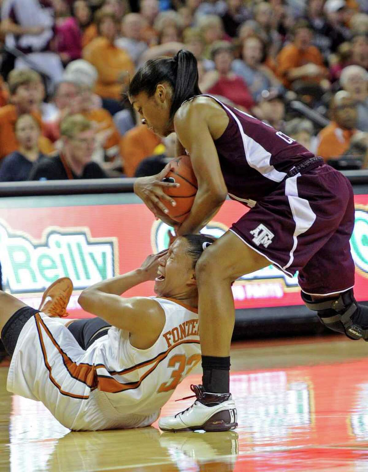 Texas A&M guard Sydney Colson, standing, took the ball away from Texas guard Ashleigh Fontenette, below, during the second half of an NCAA college basketball game Sunday, Feb. 27, 2011, in Austin, Texas. Texas A&M won 68-65.