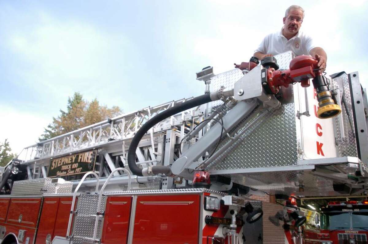 Chief Mike Klemish points out some of the new features on Stepney Volunteer Fire Company's new 2009 lader tower, one of six new trucks for the Monroe, Conn. fire company.