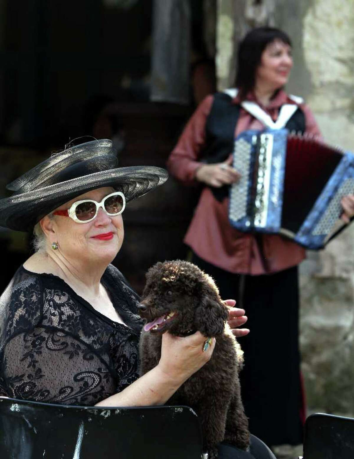 Bettie Ward holds her French poodle named Remember as an accordionist serenades the crowd at the San Antonio French Cultures Festival on Sunday. The event, which featured cuisine from San Antonio French restaurants, French wines and cultural demonstrations, was the opener for a month of French-based events.