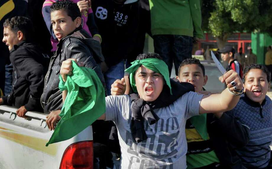 A pro-Gadhafi youth riding in the back of a pickup truck brandishes a knife, as they ride up and down chanting at a rally on the highway in Surman, west of Zawiya, 50 miles (80 kilometers) west of Tripoli, in Libya, Sunday, Feb. 27, 2011. Hundreds of armed anti-government forces backed by military defectors in Zawiya, the city closest to the capital Tripoli, prepared Sunday to repel an expected offensive by forces loyal to Moammar Gadhafi who are surrounding the city. (AP Photo/Ben Curtis) Photo: Ben Curtis / AP