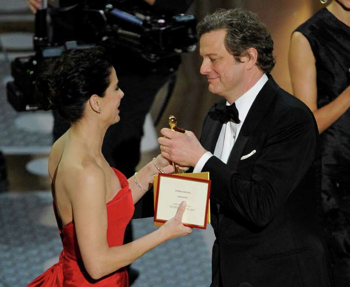 Sandra Bullock congratulates Colin Firth as he accepts the Oscar for best performance by an actor in a leading role for