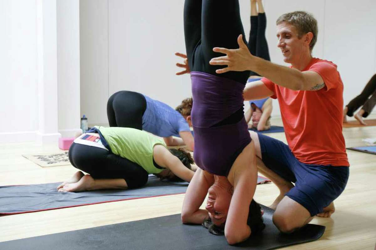 Kaia Yoga co-owner, Stan Woodman, assists student Sandy Willis during a yoga class at the new Kaia Yoga location in Westport on Thursday, June 3, 2010. Yoga studios and other businesses services are concerned a proposal to slap a sales tax on them could create some financial disharmony for clients and hurt business.