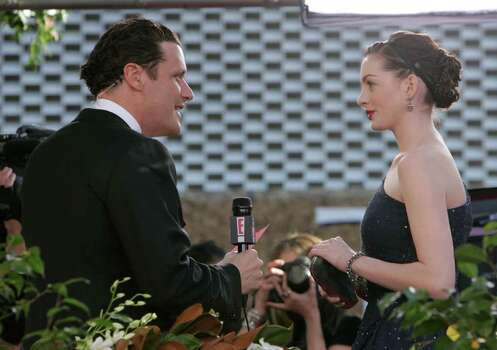 "Fashion designer Isaac Mizrahi interviews actress Anne Hathaway for"" E!"" during arrivals at the Golden Globe Awards Monday, Jan. 16, 2006, in Los Angeles. E! correspondent Mizrahi is defending his bold behavior on the carpet, where he groped Scarlett Johansson's breast and asked Eva Longoria about her pubic hair. He returns to the red carpet March 5 for the Academy Awards. Photo: KEVORK DJANSEZIAN, AP / AP"