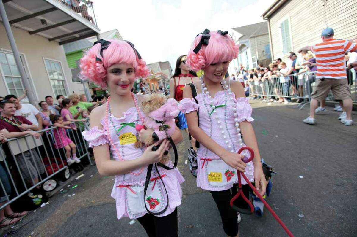 Young girls and their dogs parade through the French Quarter during the Krewe of Barkus Mardi Gras parade in New Orleans, Sunday, Feb. 27, 2011. The parade of dogs and their owners, a twist on the Krewe of Bacchus, benefits animal welfare organizations. (AP Photo/Gerald Herbert)