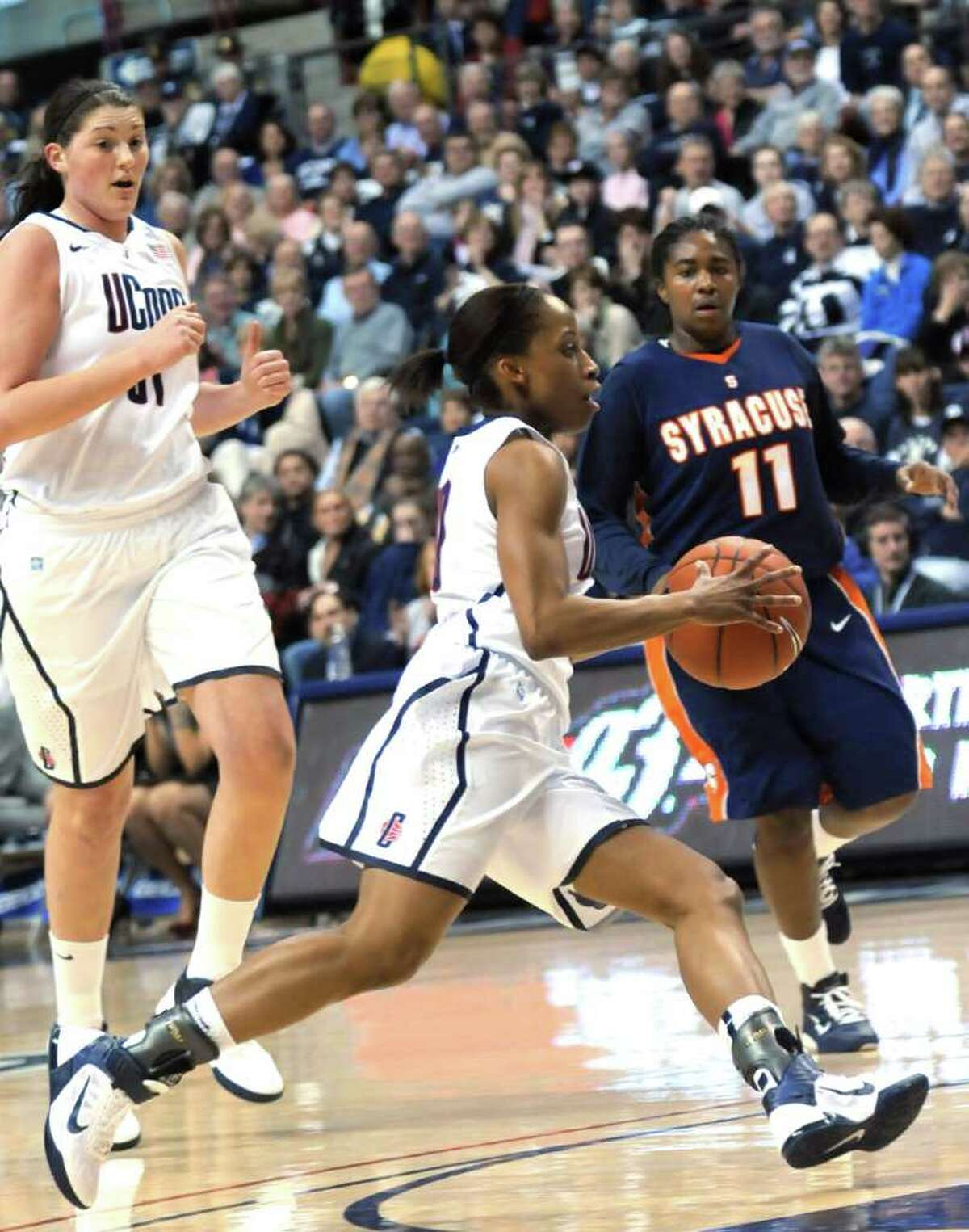 Connecticut's Lorin Dixon sprints for the basket in front of Syracuse's Tasha Harris, right, and Connecticut's Stefanie Dolson during the first half of an NCAA college basketball game in Storrs, Conn., Monday, Feb. 28, 2011. (AP Photo/Bob Child)