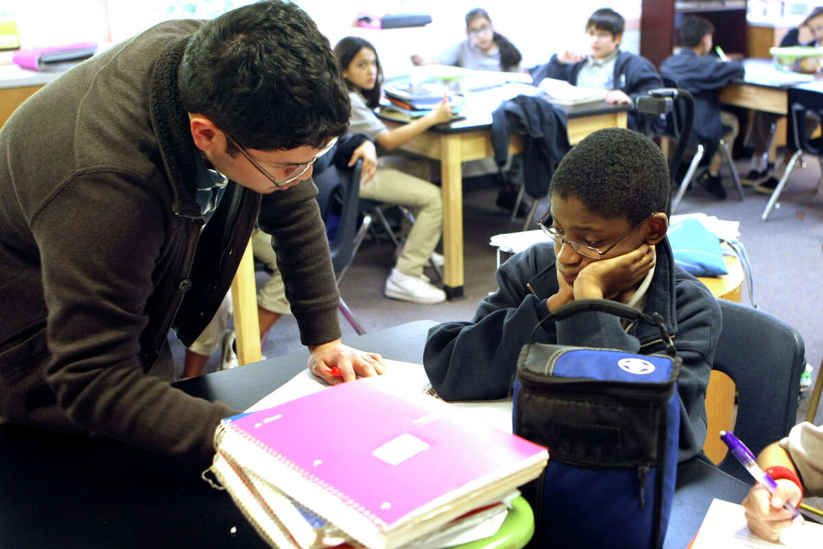 Science teacher Adam Gomez answers a question for Isaiah Dickson, 11, at KIPP San Antonio's Camino Academy, one of three schools the charter district operates.