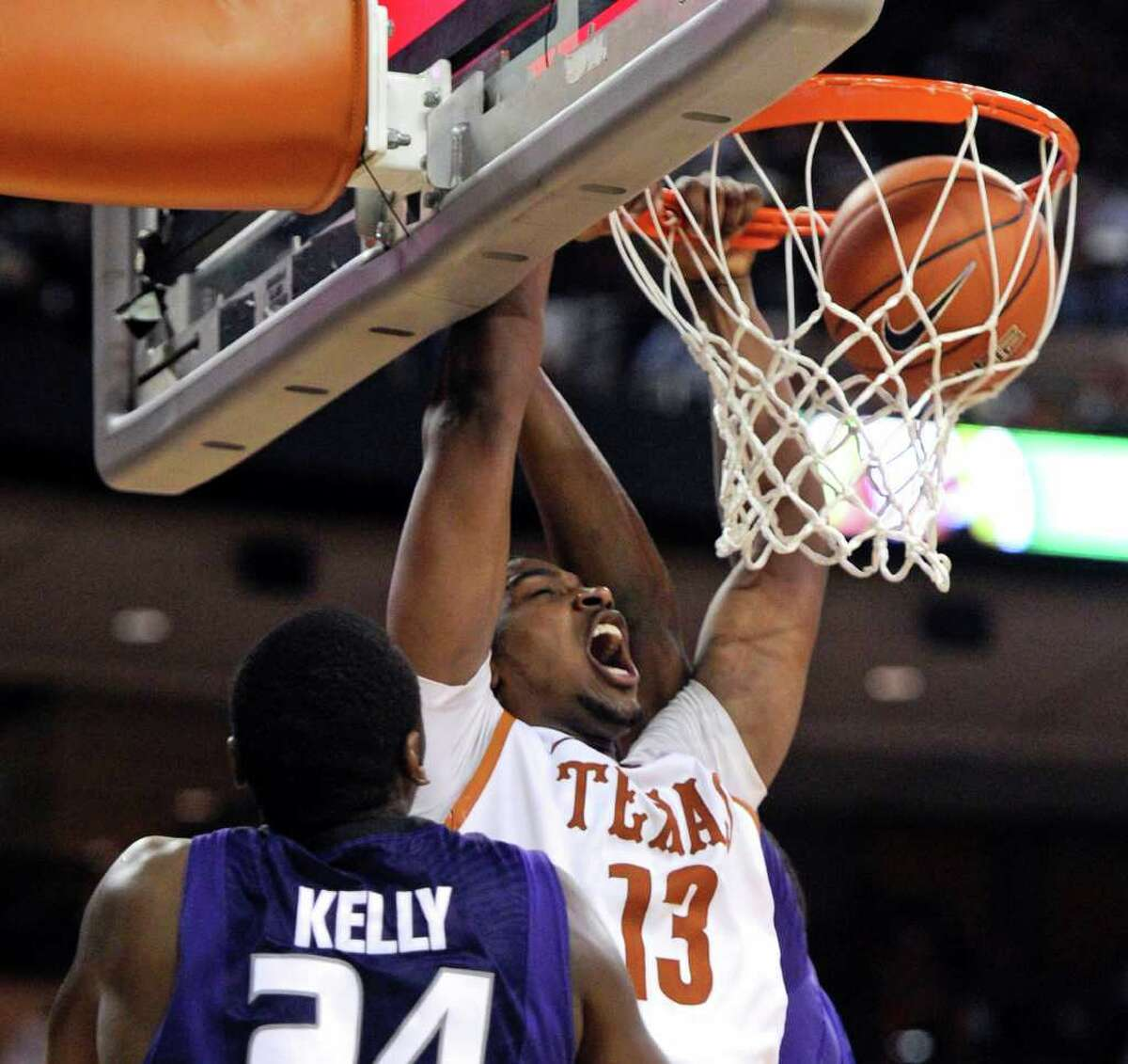 Texas forward Tristan Thompson (center) dunks the ball against Kansas State forward Curtis Kelly (front) and center Jordan Henriquez-Roberts (rear) during the first half on Monday, Feb. 28, 2011, in Austin.