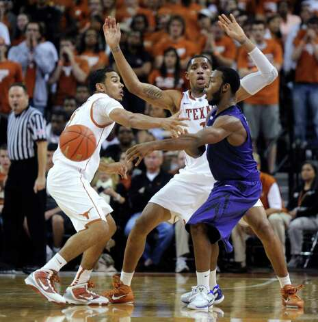 Kansas State guard Jacob Pullen (right) passes the ball around Texas guard Cory Joseph (left) and forward Gary Johnson (back) during the first half on Monday, Feb. 28, 2011, in Austin. Photo: Michael Thomas/Associated Press