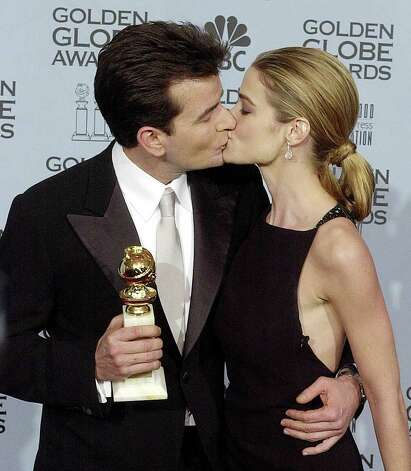 "BEVERLY HILLS, UNITED STATES:  Actor Charlie Sheen (L) kisses fiancee actress Denise Richards (R) after he won a Golden Globe Award for Best Performance by an Actor in a Television Series-Musical/Comedy for his role in ""Spin City"" at the 59th Annual Golden Globe Awards at the Beverly Hilton in Beverly Hills 20 January, 2002.   AFP PHOTO/Scott NELSON Photo: Scott Nelson, AFP/Getty Images / AFP"