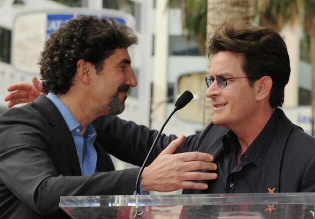 "Television producer and writer Chuck Lorre (L) is congratulated by actor Charlie Sheen (R) after Lorre received a star on the Hollywood Walk Of Fame in Los Angeles on March 12, 2009.  Lorre has produced shows such as ""Grace Under Fire"",""Dharma and Greg"", ""Two and a Half Men"" and ""The Big Bang Theory.""              AFP PHOTO/Mark RALSTON Photo: MARK RALSTON, AFP/Getty Images / 2009 AFP"