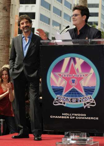"Television producer and writer Chuck Lorre listens as actor Charlie Sheen gives a speech before Lorre unveilled his star on the Hollywood Walk Of Fame in Los Angeles on March 12, 2009.  Lorre has produced shows such as ""Grace Under Fire"", ""Dharma and Greg"", ""Two and a Half Men"" and ""The Big Bang Theory"".              AFP PHOTO/Mark RALSTON Photo: MARK RALSTON, AFP/Getty Images / 2009 AFP"