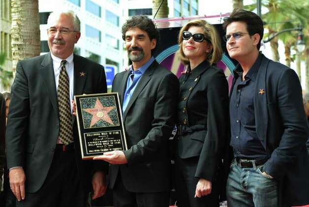 "Television producer and writer Chuck Lorre (2nd left) holds his star plaque as he poses for photos with Hollywood Chamber of Commerce official Mark Panatier (L) and actors Christine Baranski and Charlie Sheen (R) after he unveilled his star on the Hollywood Walk Of Fame in Los Angeles on March 12, 2009.  Lorre has produced shows such as ""Grace Under Fire"", ""Dharma and Greg"", ""Two and a Half Men"" and ""The Big Bang Theory"".              AFP PHOTO/Mark RALSTON Photo: MARK RALSTON, AFP/Getty Images / 2009 AFP"