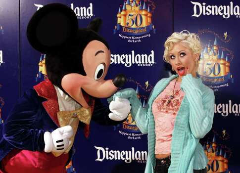 Singer Christina Aguilera reacts as Disney character Mickey Mouse kisses her hand as she arrives at Disneyland's 50th anniversary party at the Disneyland theme park Wednesday, May 4, 2005, in Anaheim, Calif. Photo: KEVORK DJANSEZIAN, AP / AP
