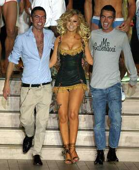 "Singer Christina Aguilera, center, walks arm-in-arm with DSquared designers, Canadian twins Dean,left, and Dan Caten at the end of their mens' fashion collection for the spring-summer 2005, unveiled in Milan, Italy, Tuesday, June 29, 2004.  ""Mr. Catenacci,"" on Dan's shirt, is in memory of the twins' late father. Photo: ANTONIO CALANNI, AP / AP"