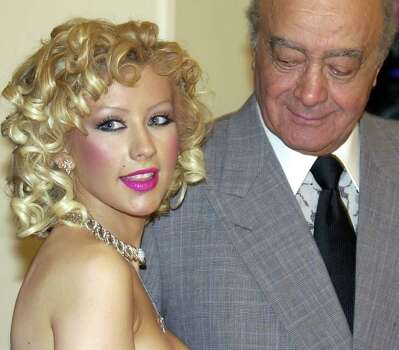 Harrods Department Store owner Mohammed al-Fayed looks down at a Piaget 18 carat white gold and diamond necklace priced down to  $32,760, from $68,432, worn by  singer Christina Aguilera during a tour of the Harrods store in London, Monday June 28, 2004.  Aguilera opened the Harrods' summer sale. Photo: RICHARD LEWIS, AP / AP
