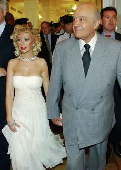 U.S singer Christina Aguilera holds the hand of Mohammed al-Fayed , owner of Harrods, during a tour of the department store in London, Monday June 28, 2004, after Aguilera opened the summer sale. Photo: RICHARD LEWIS, AP / AP