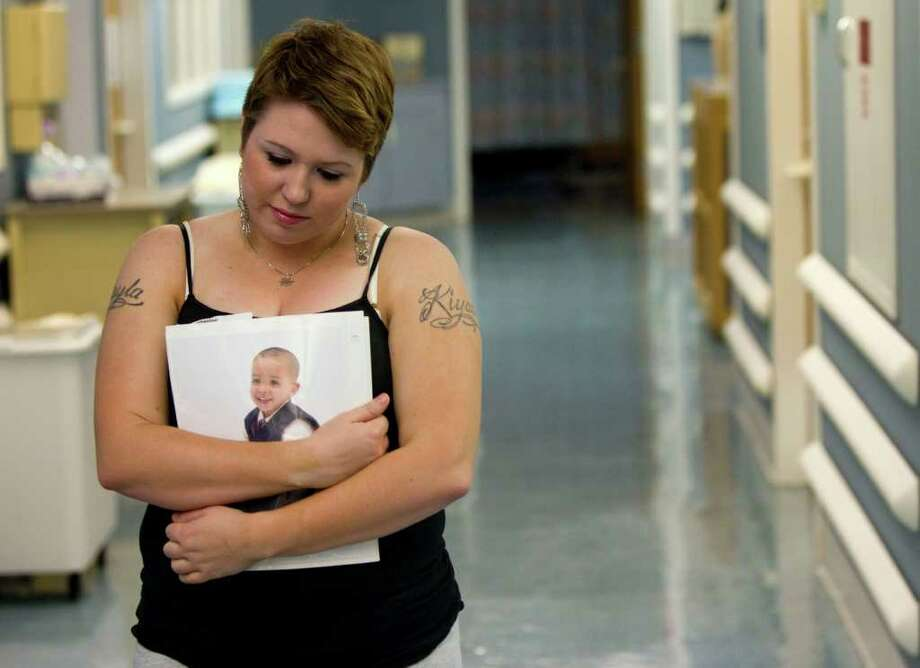 Tiffany Dickerson, 24, mother of two children who were victims of a deadly day care fire, holds a photo of her son, Shomari, as she walks down a hallway following an interview at Shriner's Burn Hospital Monday, Feb. 28, 2011, in Galveston. One of Dickerson's children, Shomari, 3, perished in the fire. A daughter, Makayla, 2, was burned in the fire and is now recovering at Shriner's Hospital. ( Brett Coomer / Houston Chronicle ) Photo: Brett Coomer, Staff / Beaumont