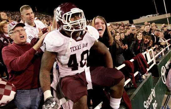 Texas A&M defensive end Von Miller (40) celebrates with fans after the Aggies held Baylor to a scoreless second half en route to a 42-30 victory in an NCAA Big XII Conference football game at Floyd Casey Stadium on Saturday, Nov. 13, 2010, in Waco. Photo: Julio Cortez, Houston Chronicle / © 2010 Houston Chronicle