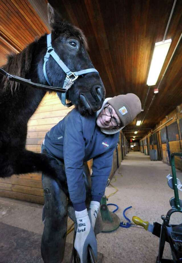 Longtime farrier Mike Kosiba, 62, shoes Kid, one of the horses of the 2nd Company Governor's Horse Guard in Newtown, Tuesday, March 1, 2011. Photo: Michael Duffy / The News-Times