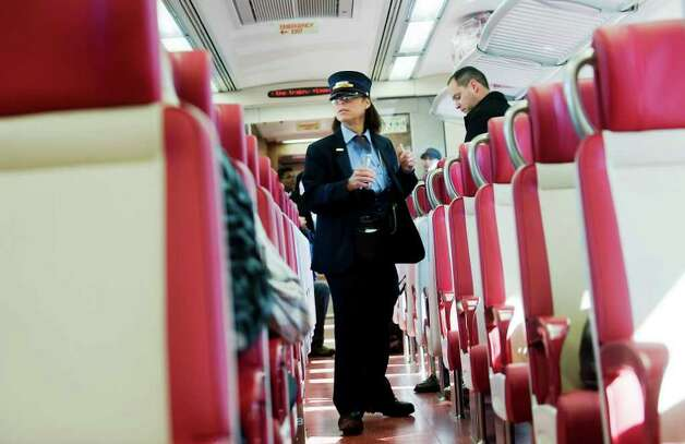Conductor Carol Kirner checks tickets as passengers ride to Grand Central Station on the inaugural run of the new M-8 train from Stamford, Conn. on Tuesday March 1, 2011. Photo: Kathleen O'Rourke / Stamford Advocate