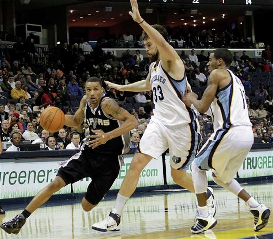 Spurs guard George Hill goes to the basket against the Grizzlies' Marc Gasol (33) and Mike Conley. (Lance Murphey/Associated Press)