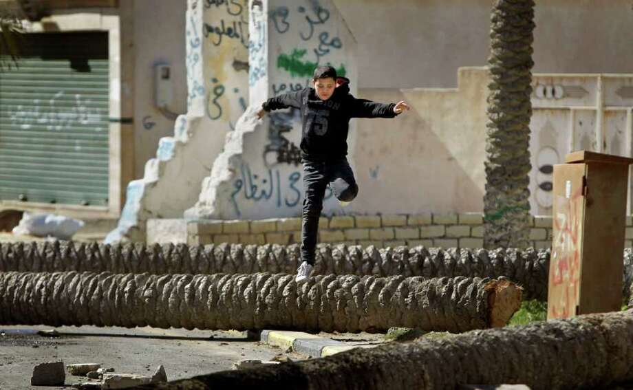 A boy leaps over felled palm trees used as roadblocks by residents in the Tajoura district of eastern Tripoli, Libya, Saturday, Feb. 26, 2011. Residents there have blocked many streets with roadblocks after protesters demanding Moammar Gadhafi's ouster came under a hail of bullets Friday when pro-regime militiamen opened fire to stop the first significant anti-government marches in days in the Libyan capital. (AP Photo/Ben Curtis) Photo: Ben Curtis / AP
