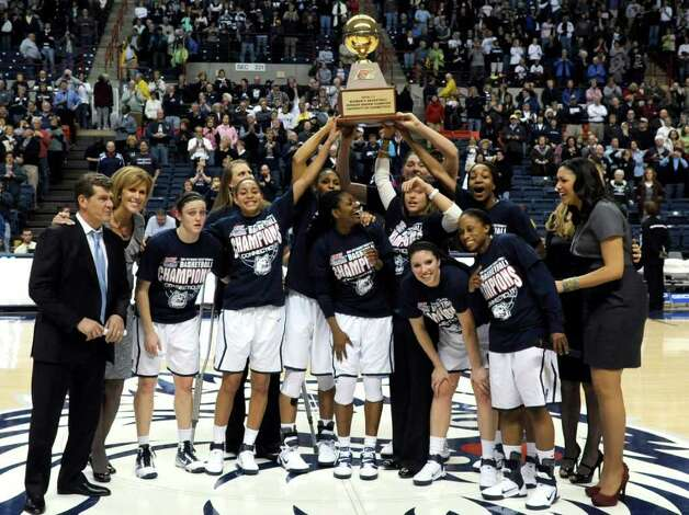 Members of the Connecticut women's basketball team hold up the Big East regular-season championship trophy after Connecticut defeated Syracuse 82-47 in an NCAA college basketball game Monday, Feb. 28, 2011, in Storrs, Conn. Coach Geno Auriemma is at left. (AP Photo/Bob Child) Photo: Bob Child