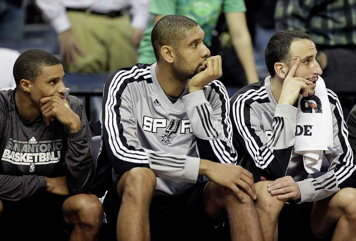 San Antonio Spurs' George Hill, Tim Duncan and Manu Ginobili, from left, watch as their team falls behind during the second half of an NBA basketball game against the Memphis Grizzlies in Memphis, Tenn., Tuesday, March 1, 2011. Memphis won 109-93.