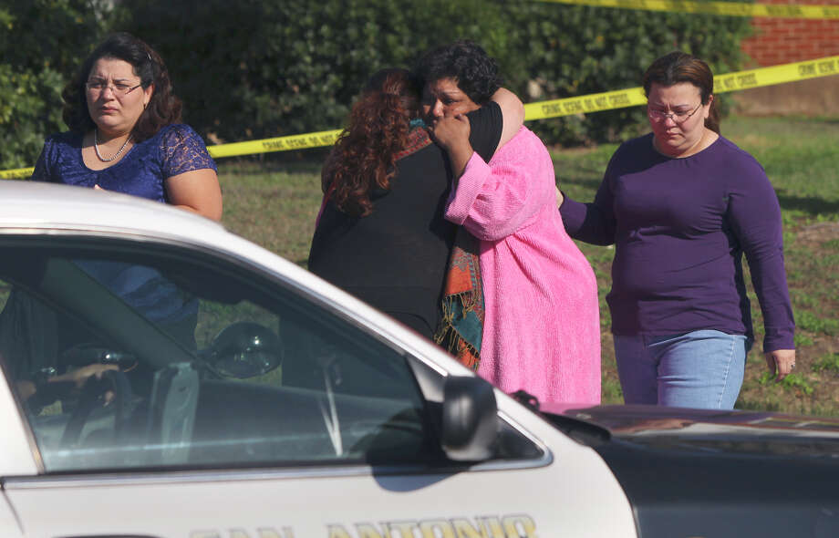 Christina Herrera (center, in pink robe) is consoled at the scene of an apartment fire where her daughter Esmeralda Herrera died early Wednesday morning March 2, 2011 at the Mitchell Village Apartments near the intersection of General Ent. Ct. and Cropsey. Police and fire officials at the scene said the 30-year-old woman's death was suspicious and is currently being investigated. Photo: John Davenport Jdavenport@express-news.net / SAN ANTONIO EXPRESS-NEWS (Photo can be sold to the public)