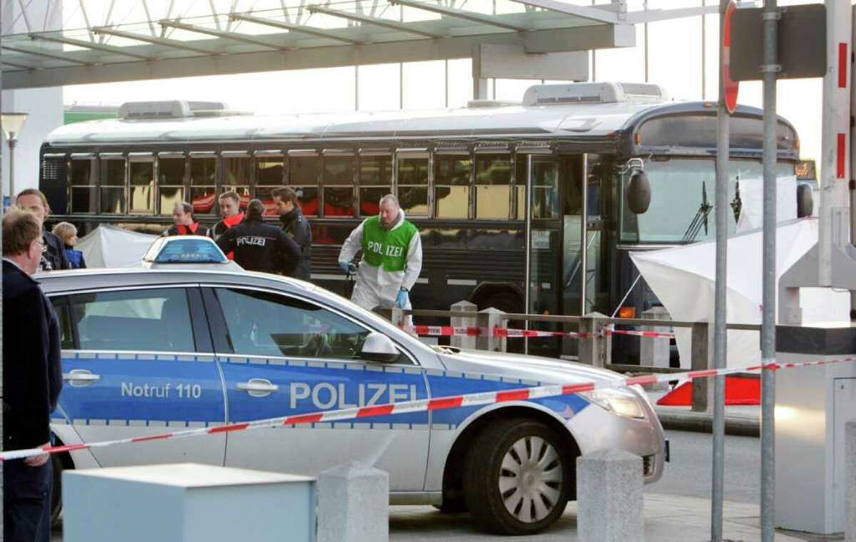 Police and paramedics work close to a bus after a gunman fired shots at U.S. soldiers on the bus outside Frankfurt airport, Germany, Wednesday, March 2, 2011 killing two people and wounding two before being taken into custody. The attack Wednesday afternoon came as the bus sat outside Terminal 2 at the airport. The two killed were the bus driver and a passenger, and that one person suffered serious wounds and one light injuries.