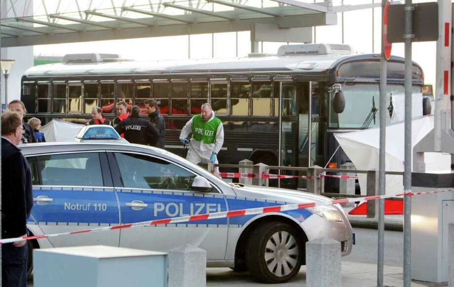 Police and paramedics work close to a bus after a gunman fired shots at U.S. soldiers on the bus outside Frankfurt airport, Germany, Wednesday, March 2, 2011 killing two people and wounding two before being taken into custody. The attack Wednesday afternoon came as the bus sat outside Terminal 2 at the airport. The two killed were the bus driver and a passenger, and that one person suffered serious wounds and one light injuries. Photo: Michael Probst, AP / AP