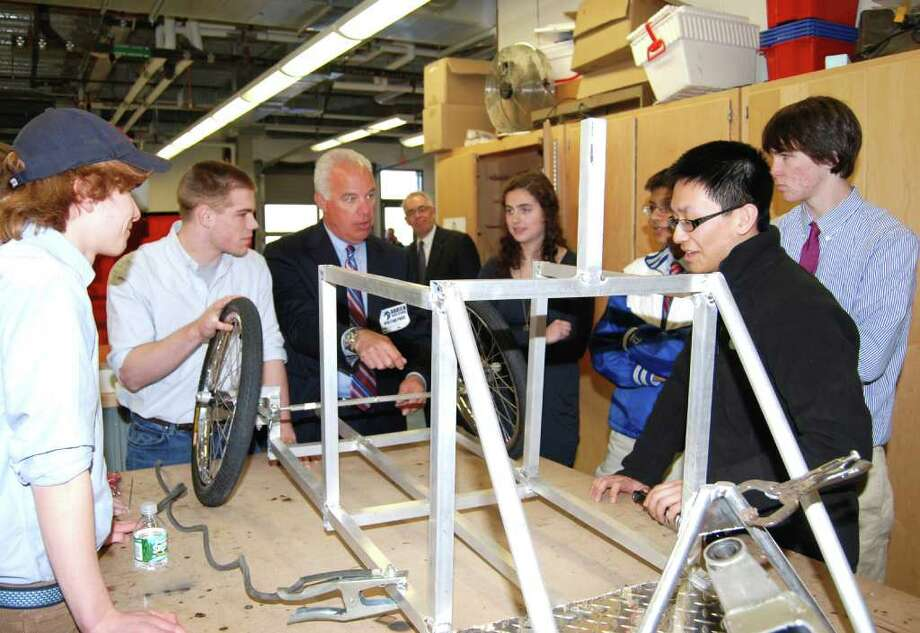 Justin Lee (on right in forefront) and Mark Juron, COO of Mercedes-Benz Greenwich (center), discuss the seat design of the Fuel Cell Car designed and built by DHS tech students. Some of those students photographed here are (l-r):  Windsor Hall, Malcolm Kiplinger, Juli Flynn, Rahul Datta and Ryan Dirvin. Photo: Jeanna Petersen Shepard / Darien News