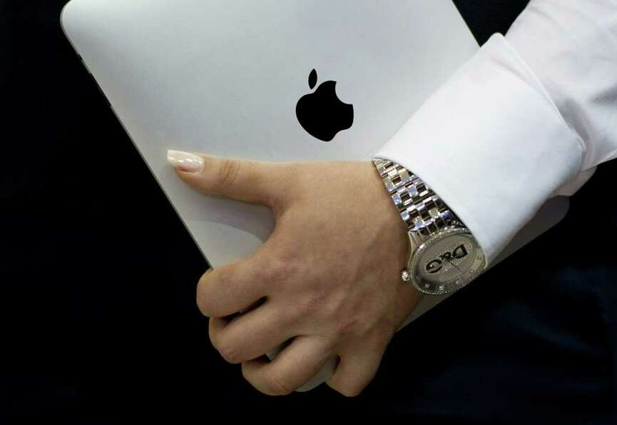 A woman wearing a watch holds an iPad at the CeBIT IT fair on its opening day on March 1, 2011 in Ha