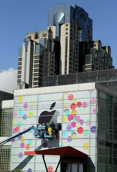 SAN FRANCISCO, CA - FEBRUARY 28:  Workers apply the Apple logo the outside of the Yerba Buena Center