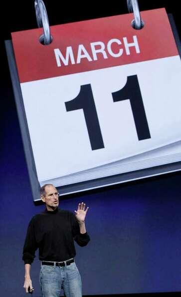 Apple Inc. Chairman and CEO Steve Jobs stands under an image for the release date of the iPad 2 at a