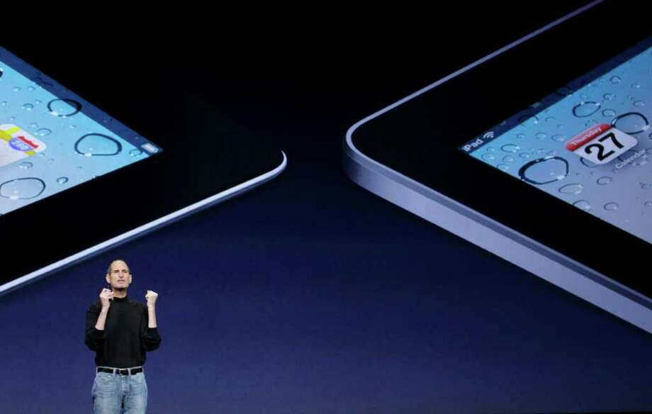 Apple Inc. Chairman and CEO Steve Jobs stands under images of the iPad 2, left, and the iPad at an Apple event at the Yerba Buena Center for the Arts Theater in San Francisco, Wednesday, March 2, 2011. (AP Photo/Jeff Chiu) Photo: Jeff Chiu