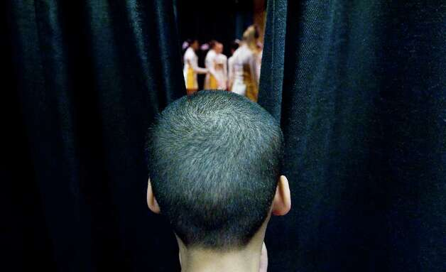 Daniel Polanco, 10, peaks through the curtain backstage as the Wethill High School cheerleaders perform at K.T. Murphy Elementary School for a pep rally in preparation for next week's Connecticut Mastery Tests in Stamford, Conn. on Wednesday March 2, 2011. Photo: Kathleen O'Rourke / Stamford Advocate