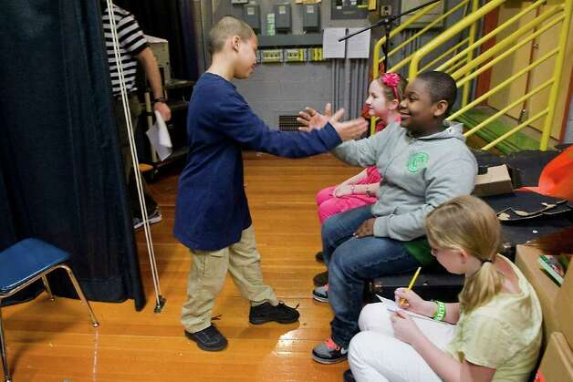 Daniel Polanco, 10, shakes hands with KJ Confident, 10, as they wait backstage with Avery Friedman, 9,  and Nikki Newcomer, 9, at K.T. Murphy Elementary School before the start of a pep rally in preparation for next week's Connecticut Mastery Tests in Stamford, Conn. on Wednesday March 2, 2011. Photo: Kathleen O'Rourke / Stamford Advocate