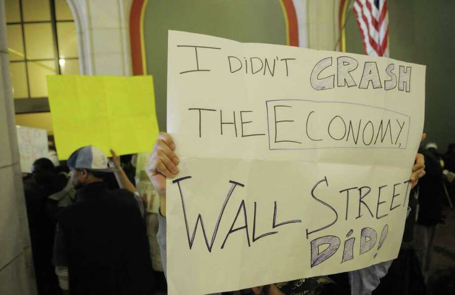A protester holds up his sign as members with the group Vocal New York blocked entrances inside the Capitol just off of State Street on Wednesday, March 2, 2011.  Several of the protesters were arrested.   (Paul Buckowski / Times Union) Photo: Paul Buckowski