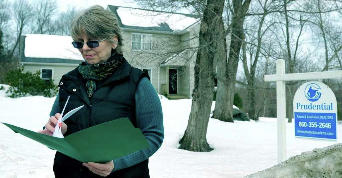 SPECTRUM/Realtor Andrea Swiedler leafs through her information in front of a recwntly sold home on Forest Drive in New Milford. Feb. 17, 2011.