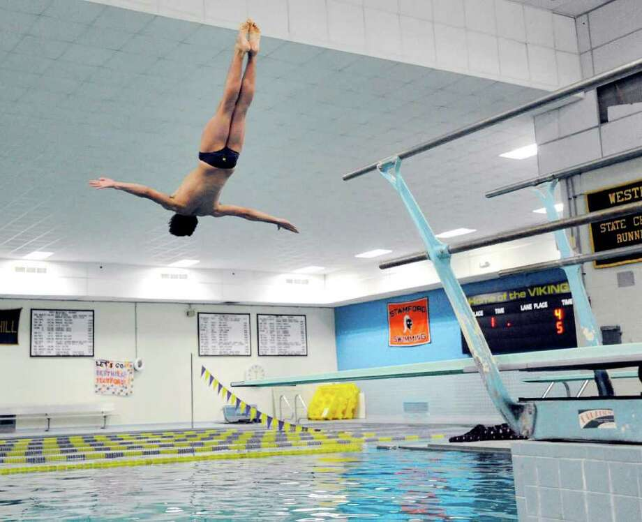 Connor Brisson of Greenwich High School floats through the air before hitting the water while competing in the FCIAC Diving finals at Westhill High School, Stamford, Wednesday night, March 2, 2011. Read the story here. Photo: Bob Luckey / Greenwich Time