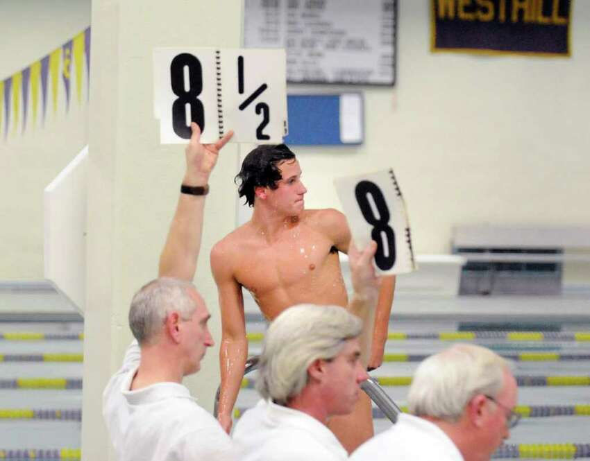 Connor Brisson of Greenwich High School looks across the pool to see his score from the other set of judges after finishing a dive during the FCIAC Diving finals at Westhill High School, Stamford, Wednesday night, March 2, 2011.