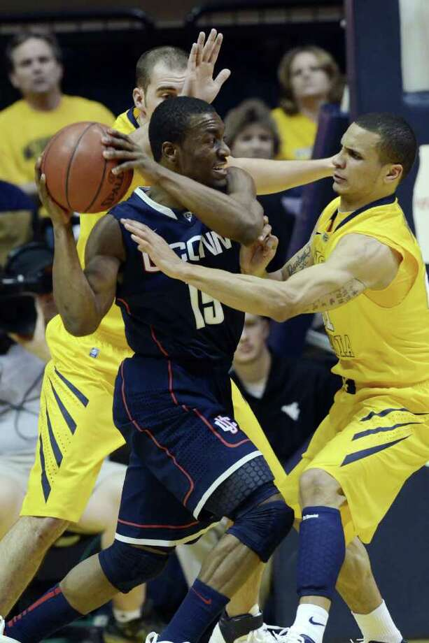 Connecticut's Kemba Walker, center, looks for a pass around West Virginia's Cam Thoroughman, left, and Joe Mazzulla, right, Wednesday, March 2, 2011, during the first half of an NCAA college basketball game in Morgantown, W.Va. (AP Photo/Jeff Gentner) Photo: AP
