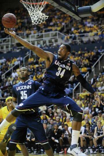 Connecticut's Alex Oriakhi (34) pulls down a rebound against West Virginia, Wednesday, March 2, 2011