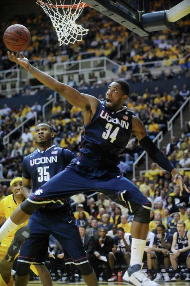 Connecticut's Alex Oriakhi (34) pulls down a rebound against West Virginia, Wednesday, March 2, 2011, during the first half of an NCAA college basketball game in Morgantown, W.Va. (AP Photo/Jeff Gentner) Photo: AP