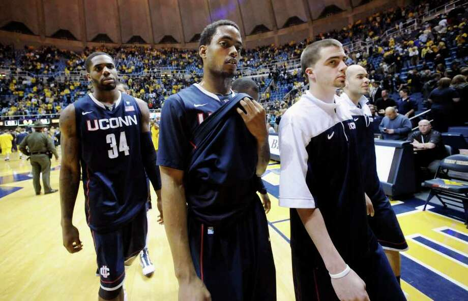 From left to right, Connecticut's Alex Oriakhi (34), Jamal Coombs-McDaniel, Kyle Bailey and Benjamin Stewart exit the court following a 65-56 loss to West Virginia, Wednesday, March 2, 2011, during an NCAA college basketball game in Morgantown, W.Va. (AP Photo/Jeff Gentner) Photo: AP