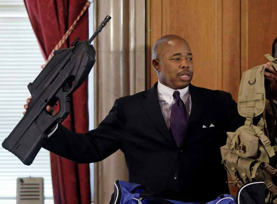 Sen. Eric Adams, D-Brooklyn, holds a firearm during a news conference at the Capitol in Albany, N.Y., on Wednesday, March 2, 2011. Adams, a former New York City police captain and owner of three guns, says the state should outlaw 30-bullet clips for them to help prevent another incident like the Arizona shooting that killed six people and wounded a congresswoman and 12 others. (AP Photo/Mike Groll) Photo: Mike Groll